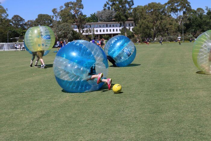 People playing bubble soccer on a field.