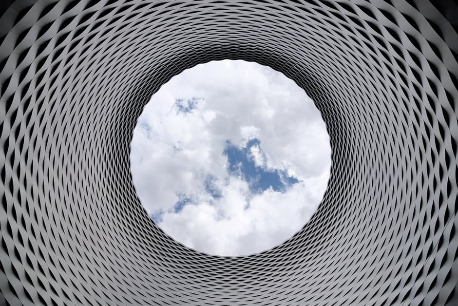 Architectural structure looking up through a tunnel to the sky.