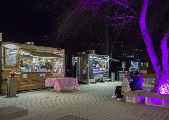 The Pop-Up deck at night with two food stalls, and an illuminated purple tree.