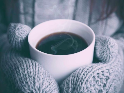 hands in mittens holding a steaming cup of black coffee