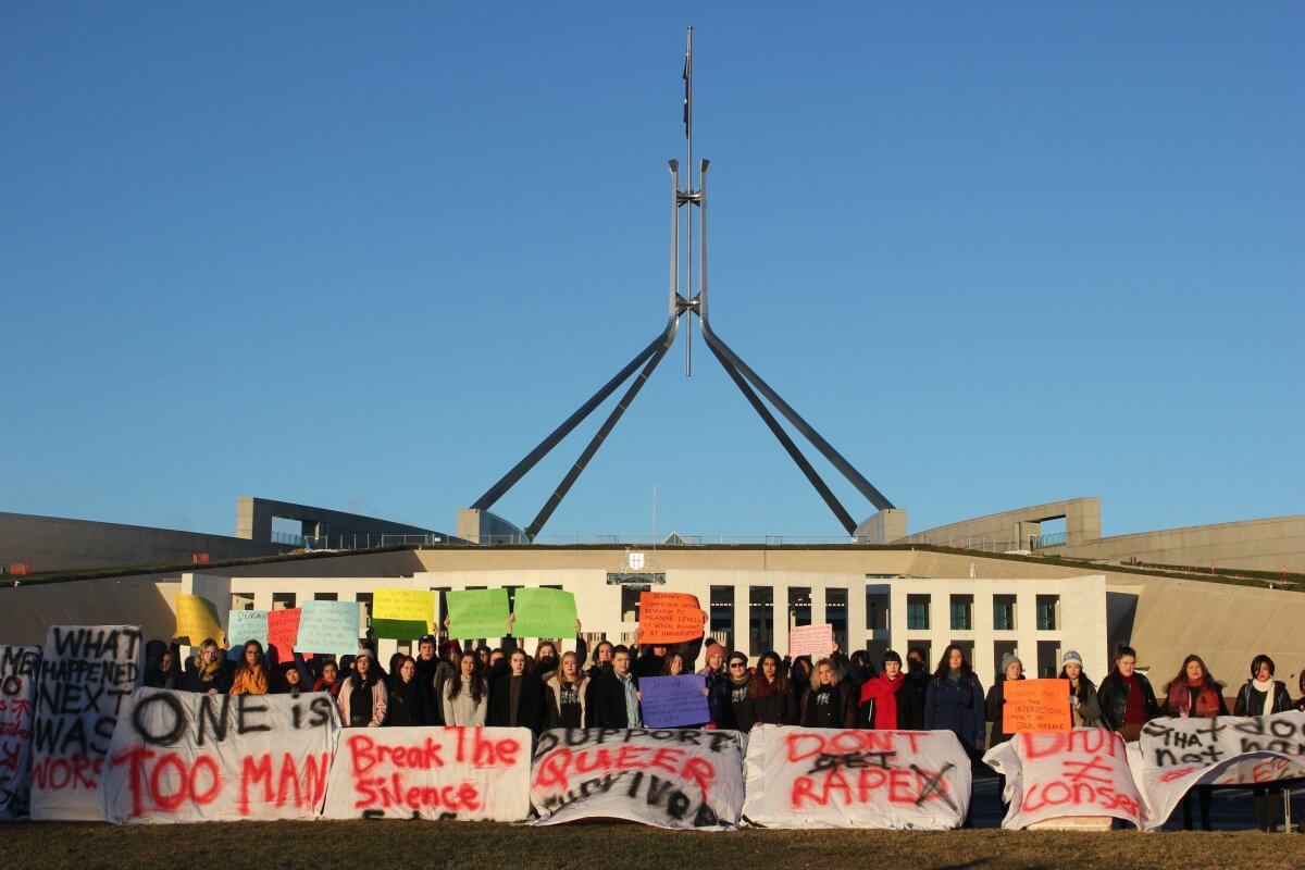Protesters outside Parliament House on Friday morning, holding mattreses with messages against sexual assault on campus.